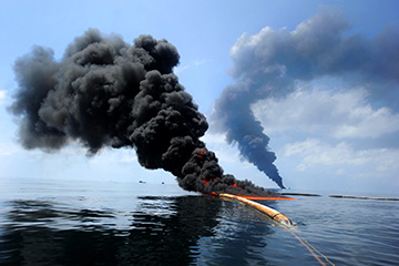 "Dark clouds of smoke and fire emerge as oil burns during a controlled fire in the Gulf of Mexico, 6 May 2010. A new study found black carbon left from the burns joined a ""dirty blizzard"" of contaminants that eventually settled on the seafloor. Photo: U.S. Navy"