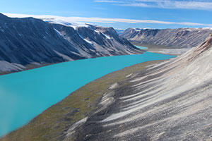 In western Greenland, small outlet glaciers are wasting backward, leaving behind piles of rocks, or moraines, that mark their previous advances. Meltwater has formed a lake. (Jason Briner)
