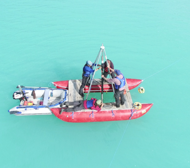 Setup of the dual boating structure used for coring. The small zodiac in the back can push the motorless coring platform into position. The platform is then anchored with local rocks during the coring process. This image is captured via drone. (M. Turrin)
