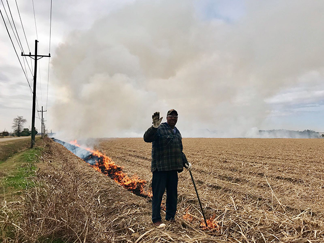 Farmers often use fire to clear agricultural fields, but the practice adds to air pollution. Here, a man tends a fire in a Louisiana field. Photo: Chloe Gao