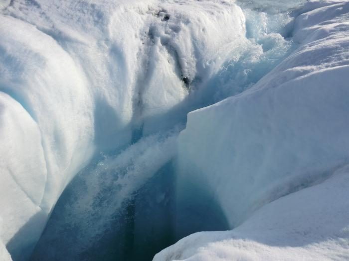 Meltwater from the Greenland ice sheet can travel through channels to reach bedrock; a new study shows where the water goes. Here, water plunges down a moulin, or hole in the ice.(Marco Tedesco/Lamont-Doherty Earth Observatory)