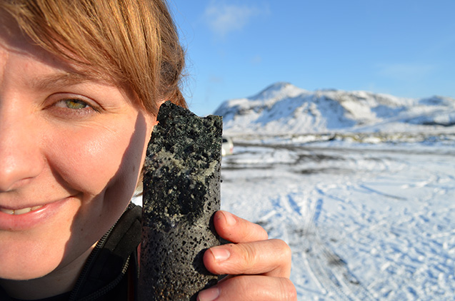 An experimental drill core held by coauthor Sandra Snaebjornsdottir is laced with solidified carbonate, apparently produced by a new process that turns carbon emissions to stone when pumped underground. (All photos: Kevin Krajick/Lamont-Doherty Earth Observatory)