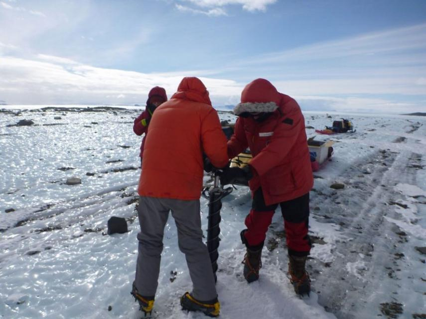 Team members taking a short ice core to study properties of sediment coming from the East Antarctic ice sheet. Image: Mike Kaplan