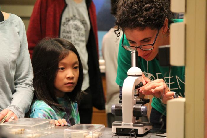 Microfossils play important roles in understanding ocean and climate history. Yael Kiro sets up a microscope for a young visitor.