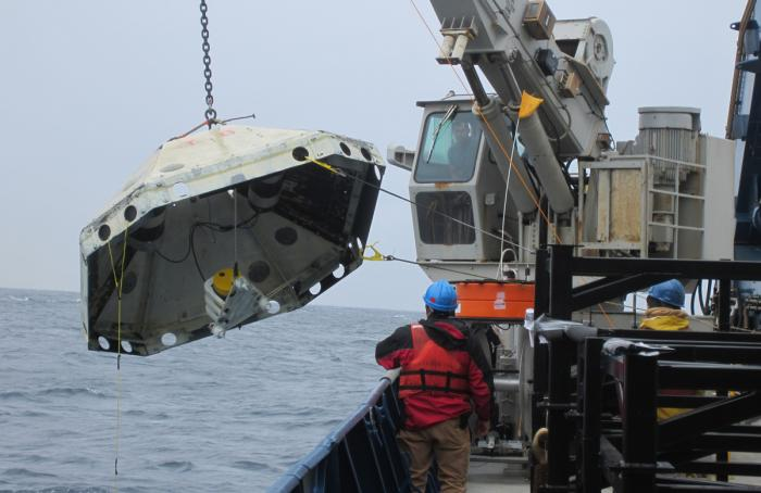 A shipboard crane lifts a Lamont-built ocean bottom seismometer attached to a protective trawler shield. Photo: Lamont-Doherty Earth Observatory
