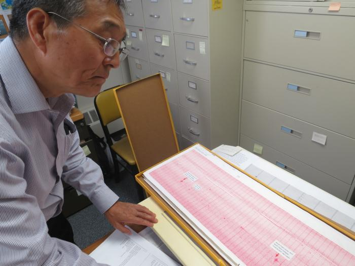 "August 22, 2016: Seismologist Won-Young Kim pulls out the original paper seismogram showing the jet impacts and subsequent collapses of the World Trade Center towers. ""It was a very painful day,"" he said. Photo: Kevin Krajick"